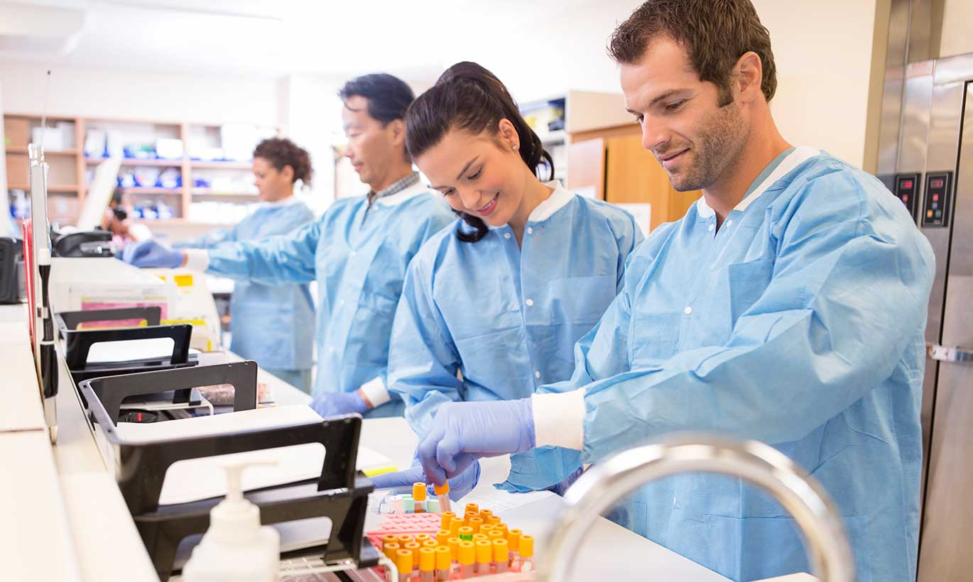 A team of lab technicians look at vials together in Houston, Texas