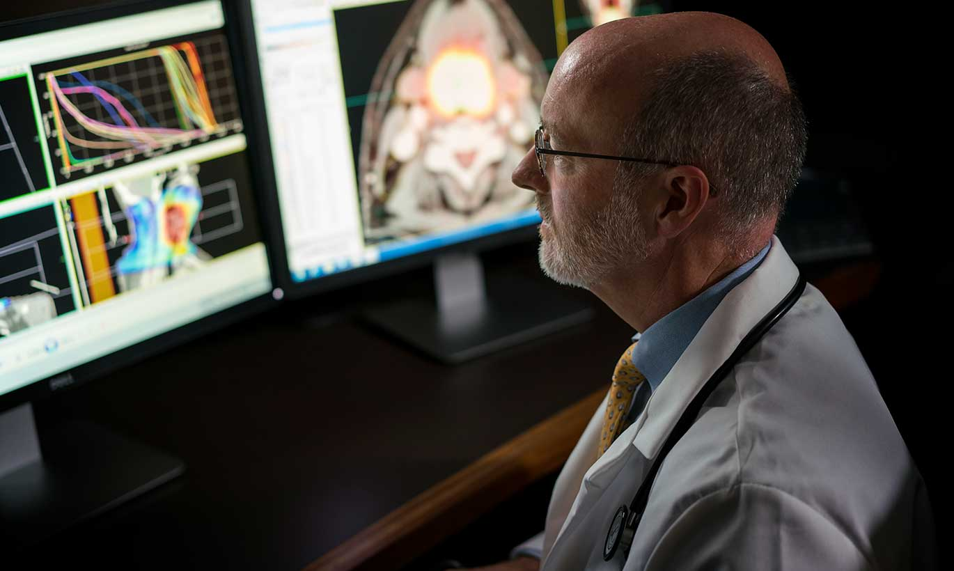 A doctor studies the results of patient tests and scans in his office in Forest Country, Texas