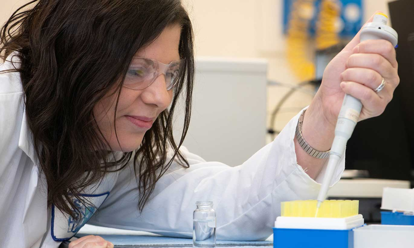 A woman at the Southwest Research Institute fills test tubes in San Antonio, Texas
