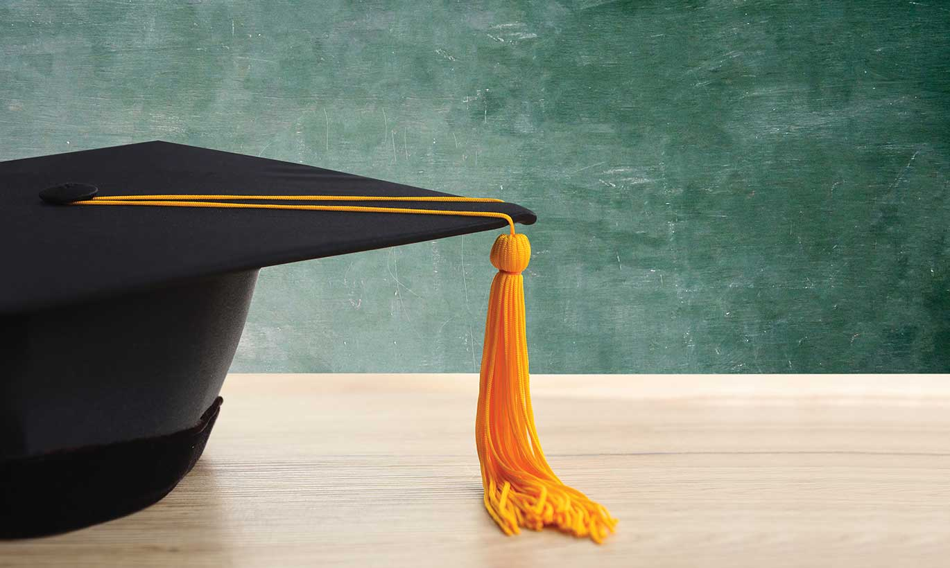A black graduation cap with a gold tassell sits in front of a chalkboard