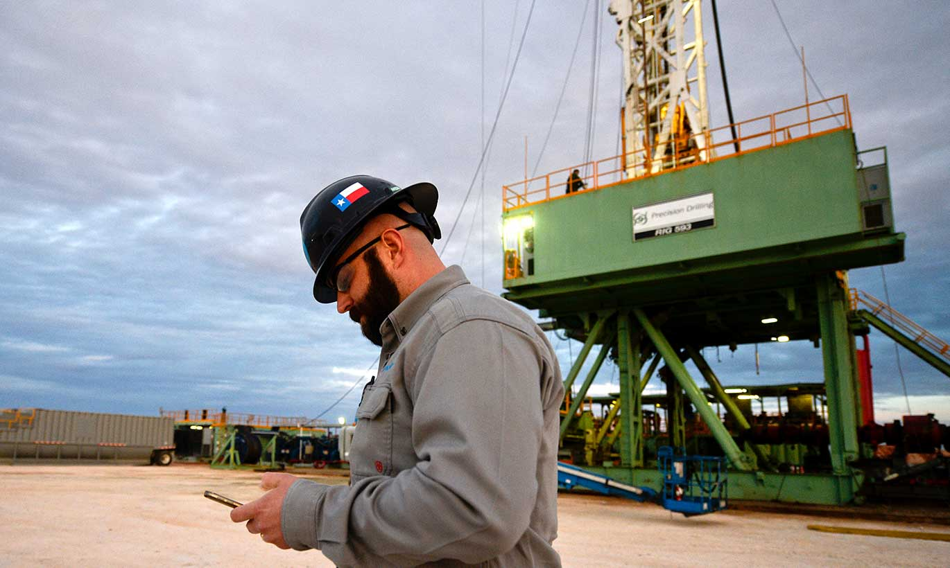 An oil and gas worker in Midland, Texas checks his phone while walking around the perimeter of the rig