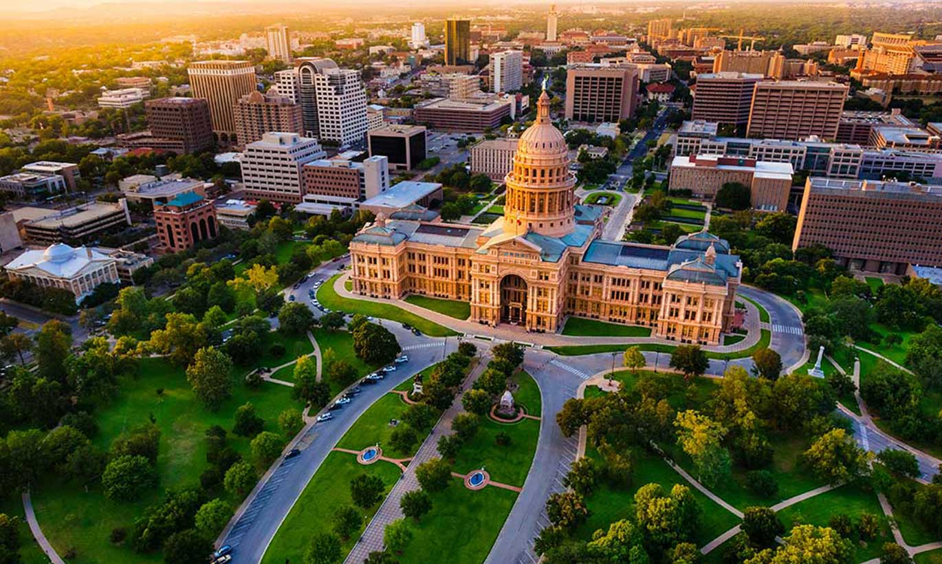 An aerial shot of the Texas Capitol building and lawn in Austin, Texas at sunset