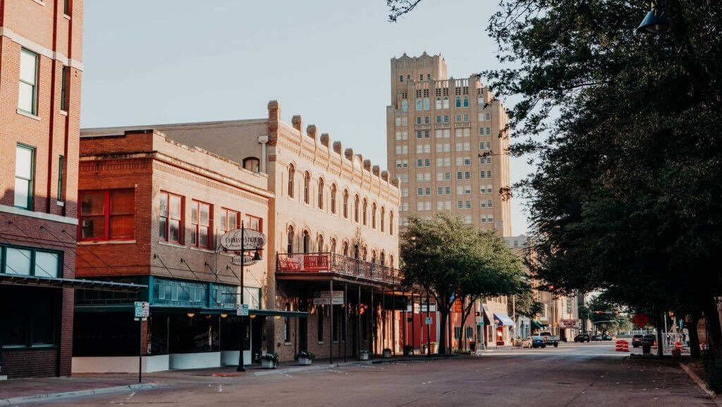 Cypress Street in downtown Abilene, Texas is lined with trees on one side and small business buildings and shops on the other side.
