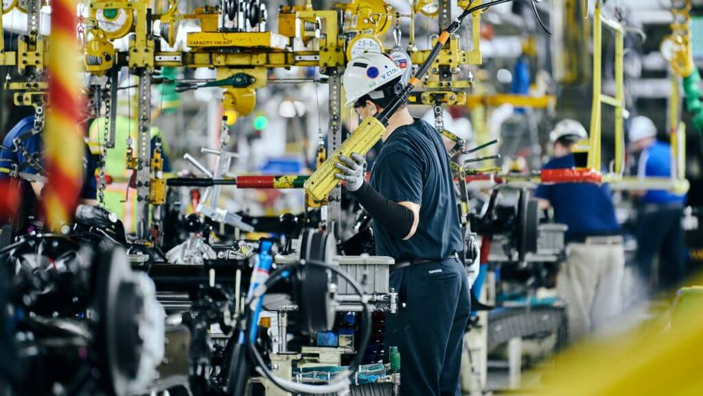 An employee at Toyota builds large machinery