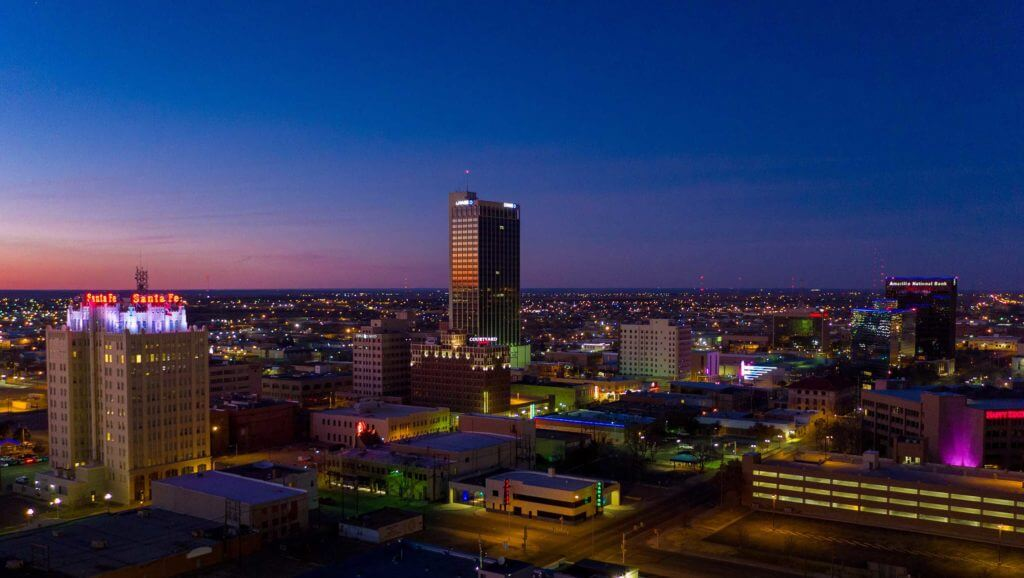 Aerial view of downtown Amarillo, Texas at night, lit up with brightly colored lights.
