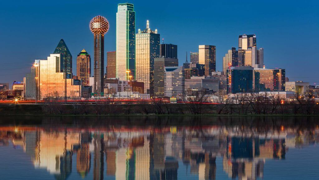 View of the Dallas skyline across the water with the buildings reflected in the water.