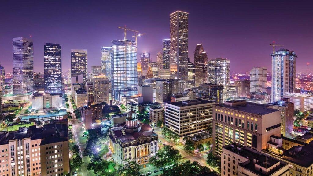 Aerial view of Houston, Texas with tall skyscrapers lit up at night.