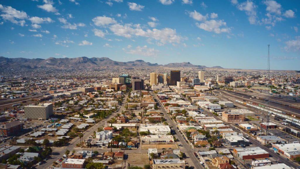 Aerial view of El Paso, Texas, with small residential buildings and large business buildings set against the backdrop of rocky mountains.