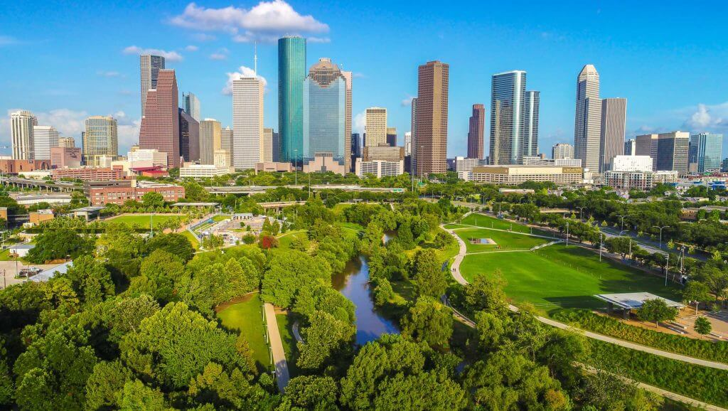 Beautiful green spaces and a river run adjacent to the tall buildings in downtown Houston, Texas.