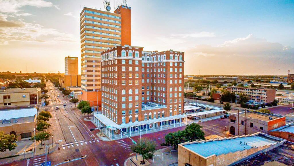 The brown Pioneer building in downtown Lubbock is seen on the corner at sunrise.