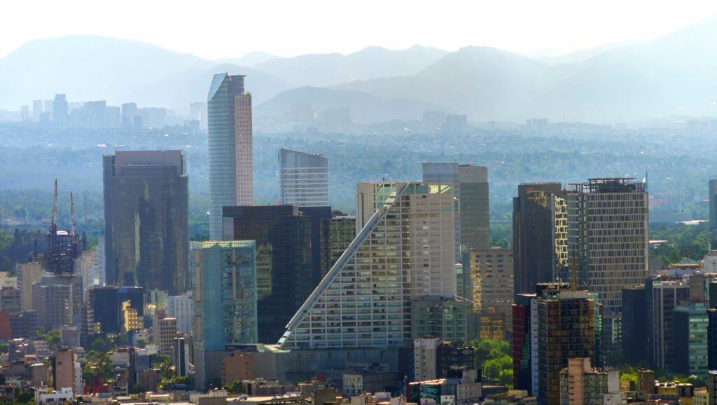 The Mexico City skyline in front of a misty range of mountains. Mexico and Texas have a very strong line of investment.