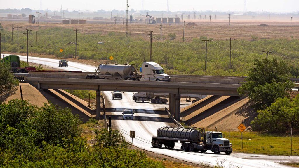 A white truck drives on an elevated overpass above another highway in Midland, Texas.