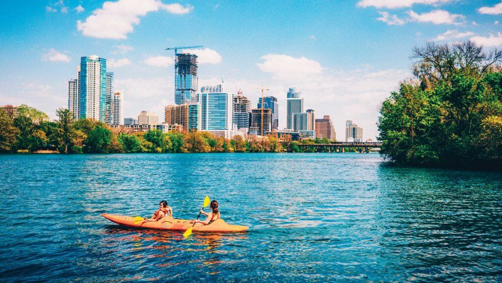 Two people in a kayak work together to paddle through a downtown river in Texas.