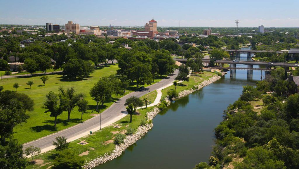 The Concho River flows alongside trees in a park near downtown San Angelo, Texas with a view of the city in the background.