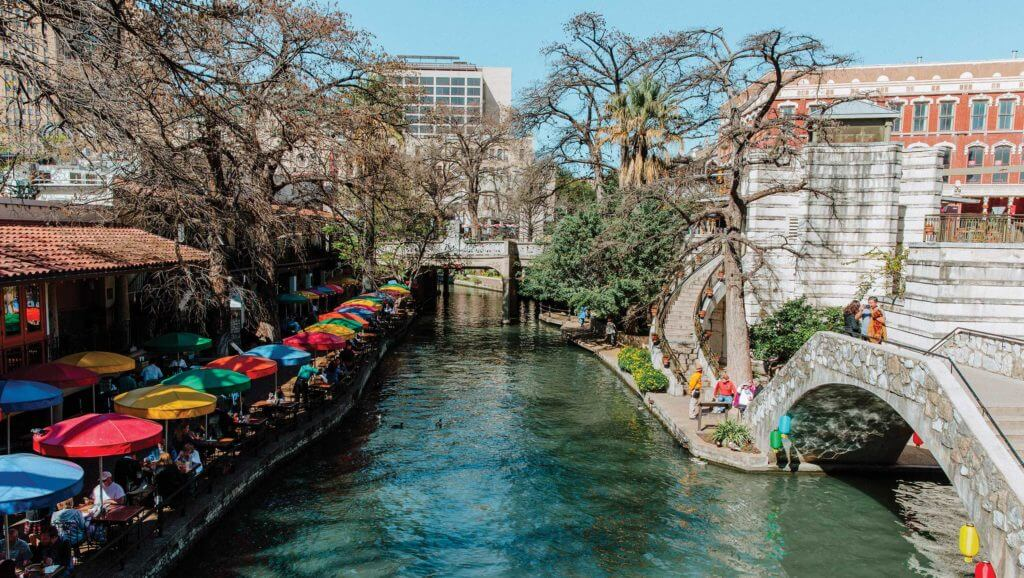 People walk alongside the San Antonio River Walk, featuring brightly colored tents and outdoor eateries.