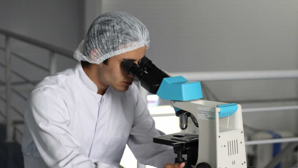 A researcher wearing a hairnet looks into a microscope.