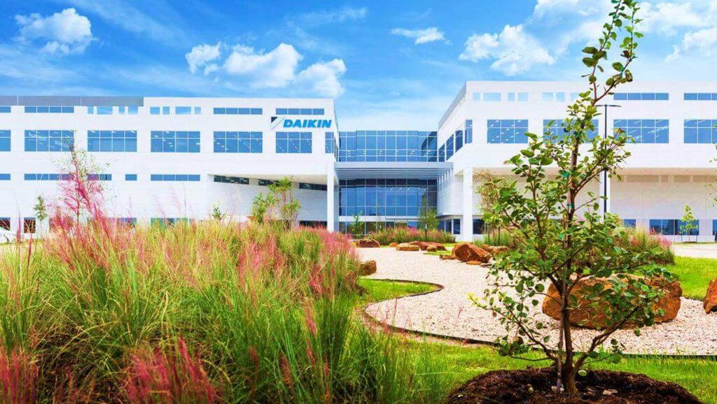 The Daikin glass building sits on a large campus with green grass and gardens.