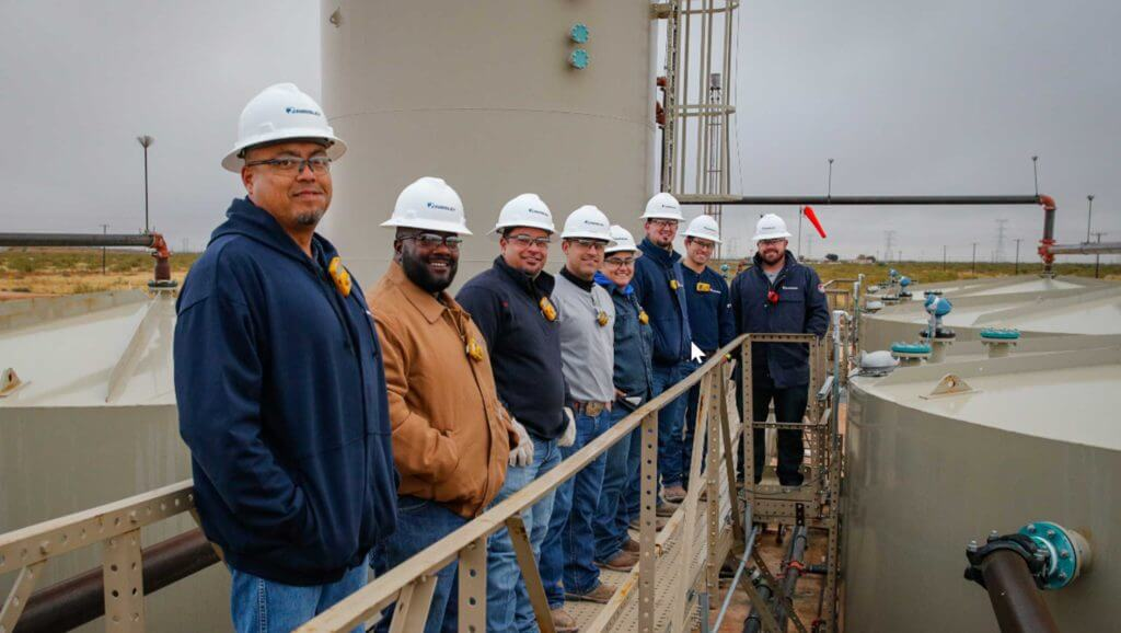 Eight people in hard hats pose for a photo at the Parsley facility.