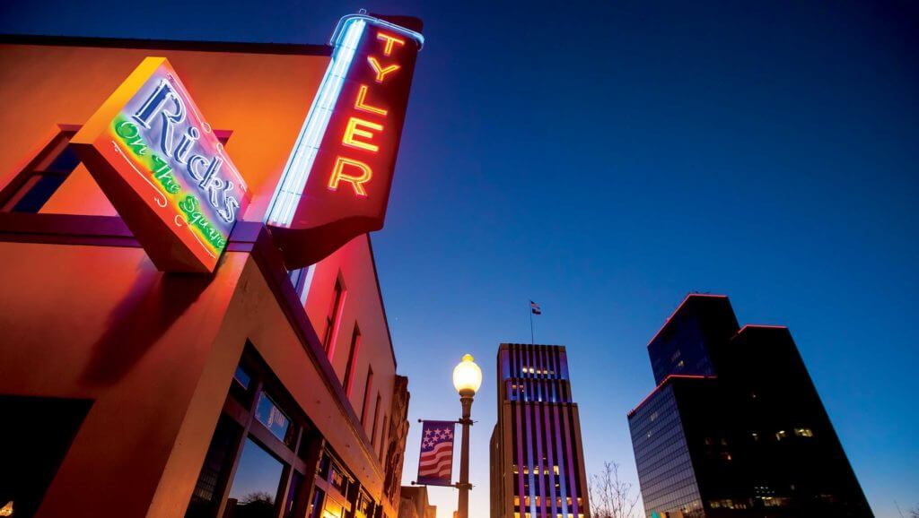 Downtown Tyler, Texas is lit up at night with neon signs.