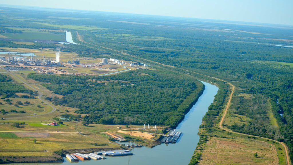 A large channel flows through the vast landscape of trees and open space at Port of Victoria, Texas.