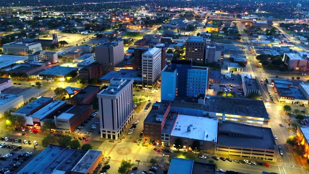 Aerial view of downtown Wichita Falls lit up at night.