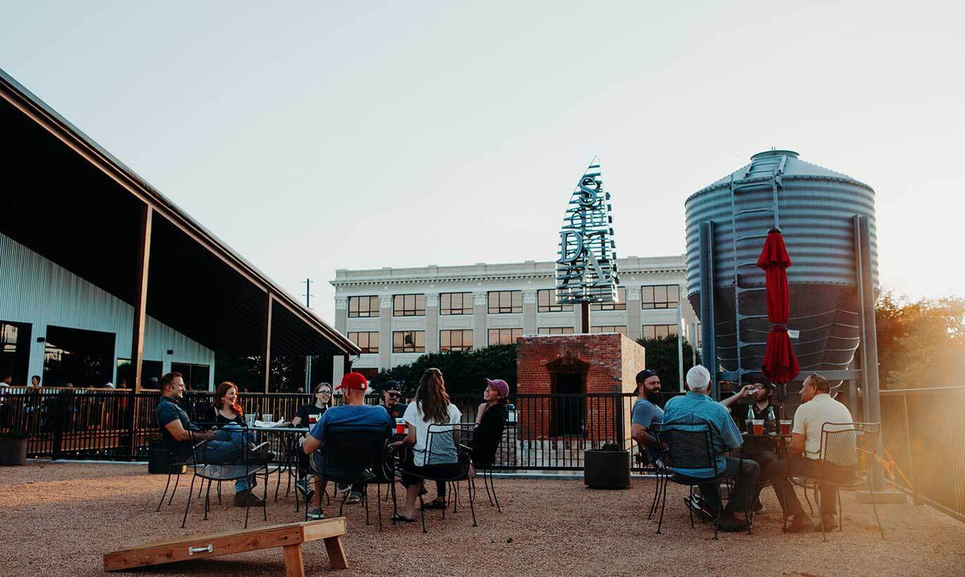 Two groups of people sit outside at large tables enjoying beers at Sockdolager Brewing Co. in Abilene, Texas.