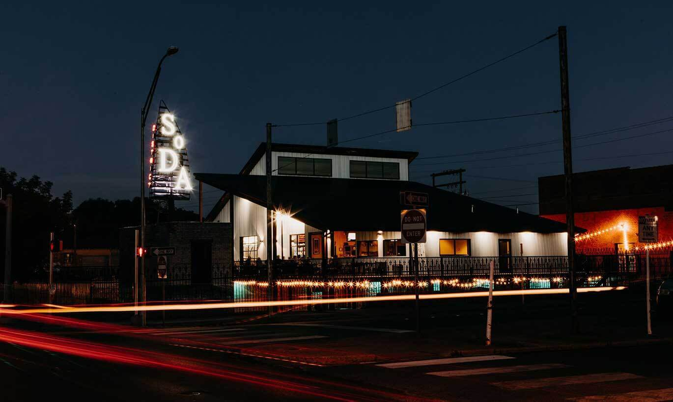 The Sockdolager Brewing Co. building is lit up at night by yellow and orange lights inside the building.