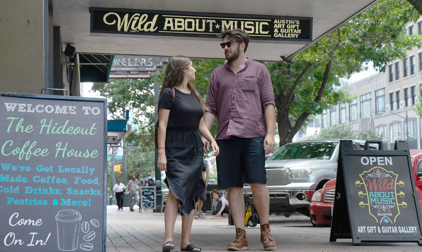A man and woman walk down the sidewalk in front of a coffeeshop in Austin, Texas.