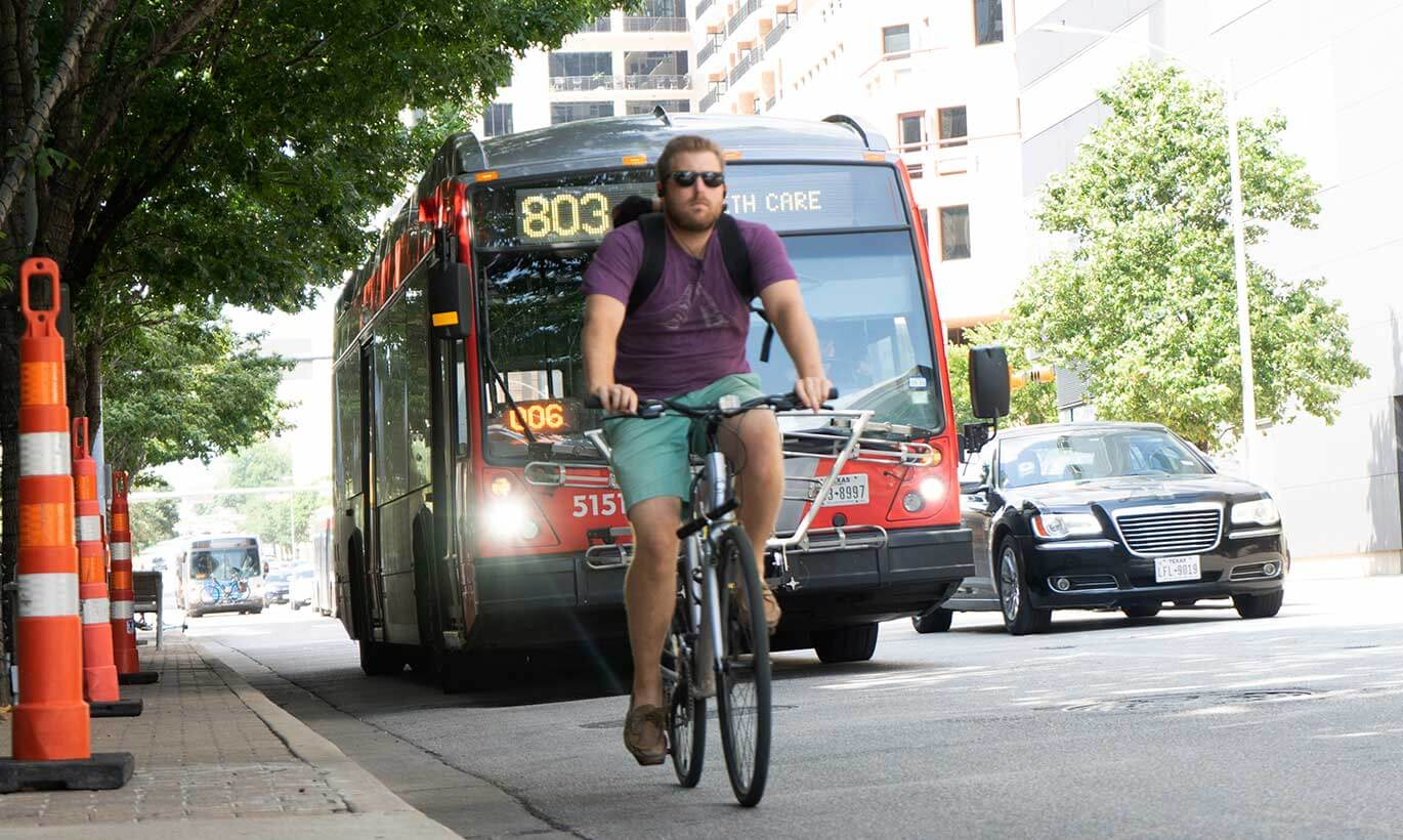 A man rides his bicycle next to a bus in downtown Austin, Texas.