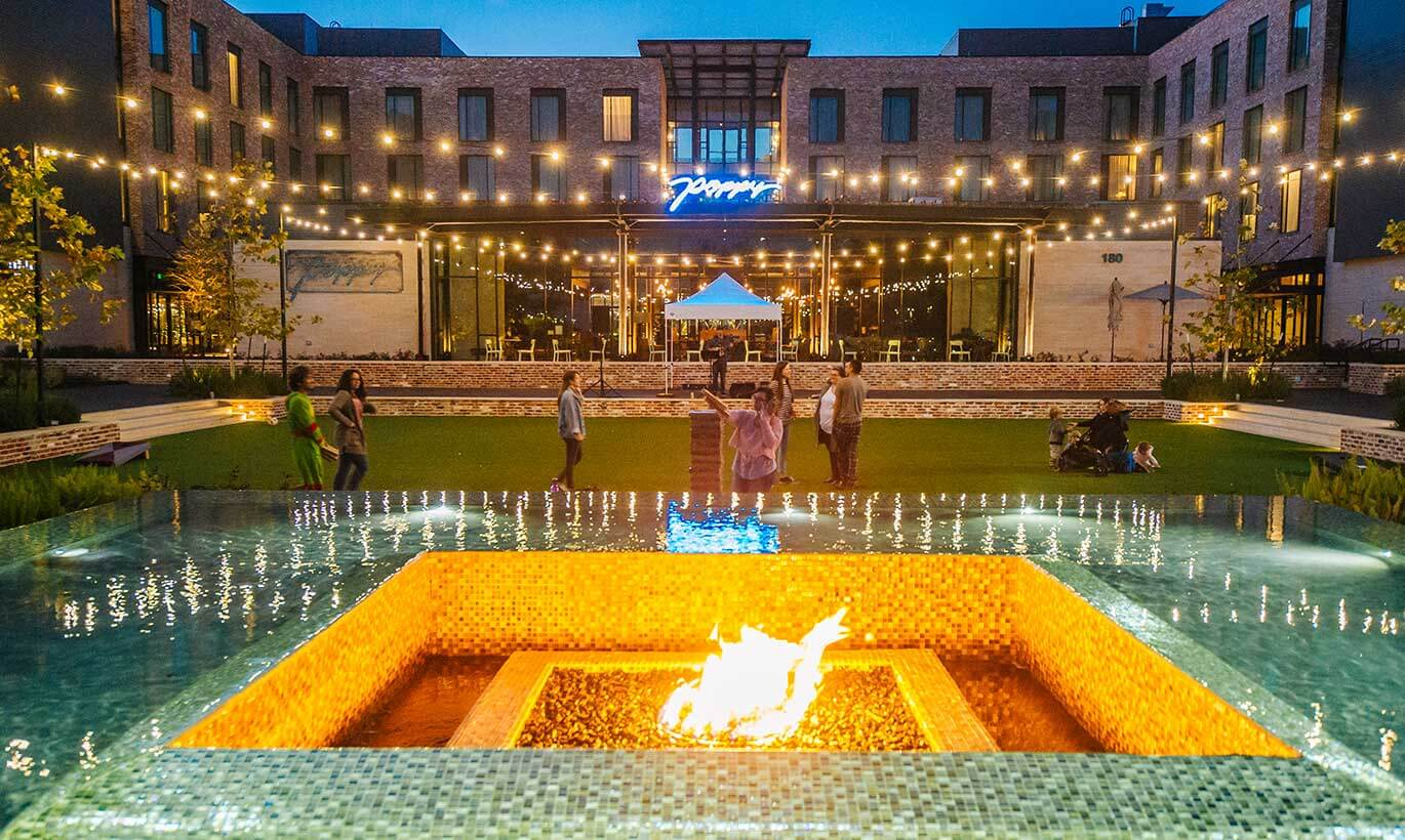 Young people and families relax outside next to a firepit at the Century Square mixed-use destination in College Station, Texas.