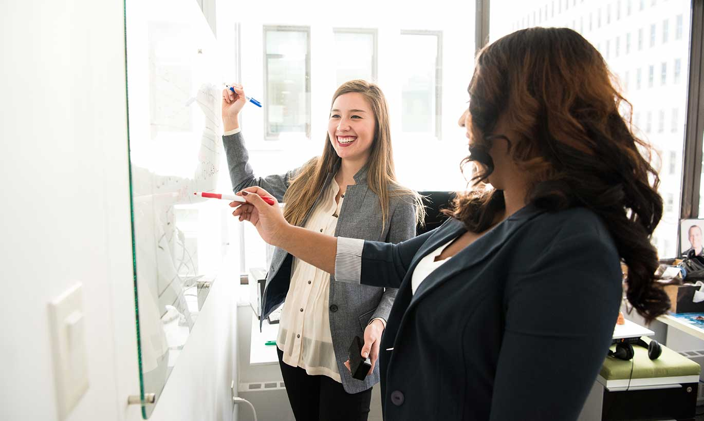 Two women in business clothing write on a whiteboard with Expo markers while talking and smiling.