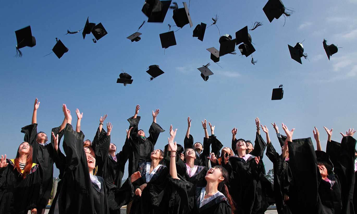 College students throw their caps into the air at a graduation ceremony.