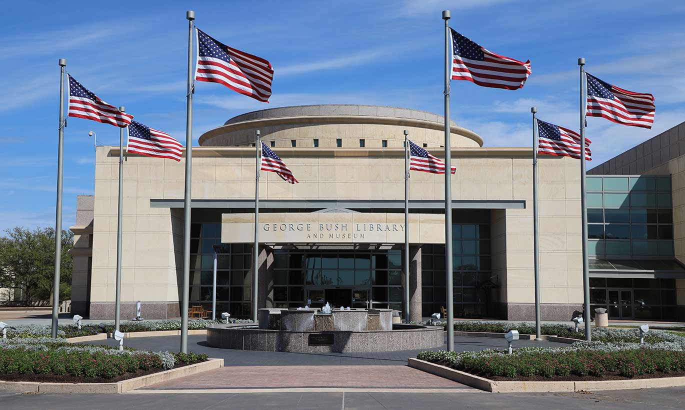 Eight American flags fly high outside of the George Bush Library and Museum in College Station, Texas.