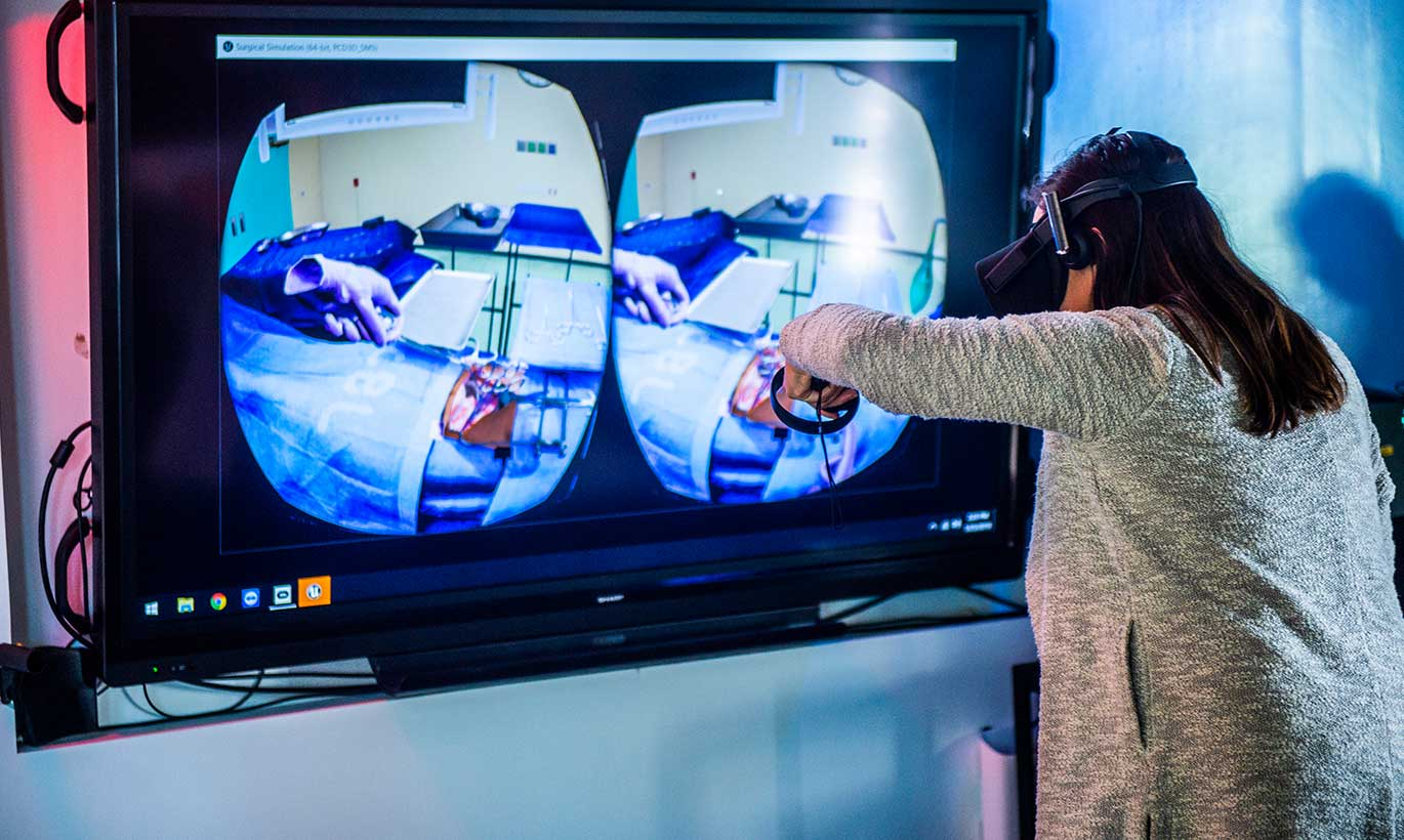 A woman wearing a headset tests a virtual reality device at Southern Methodist University.