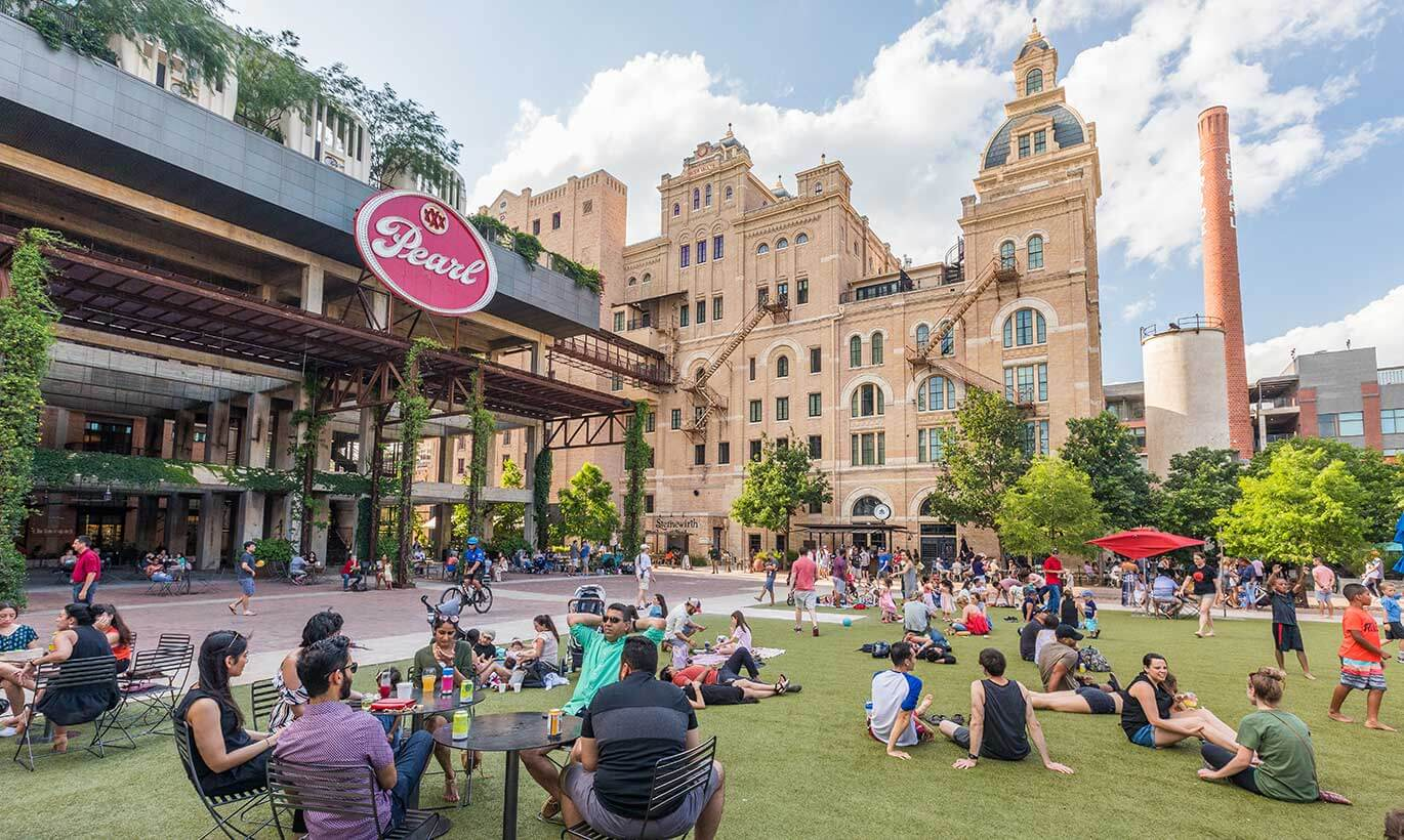 Groups of people occupy a large greenspace outside of Pearl Brewery in San Antonio, Texas.
