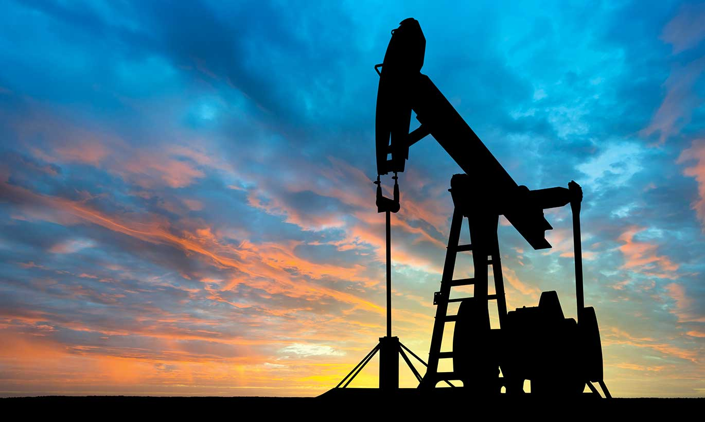 The silhouette of a large oil pump with a sunset backdrop in Texas.