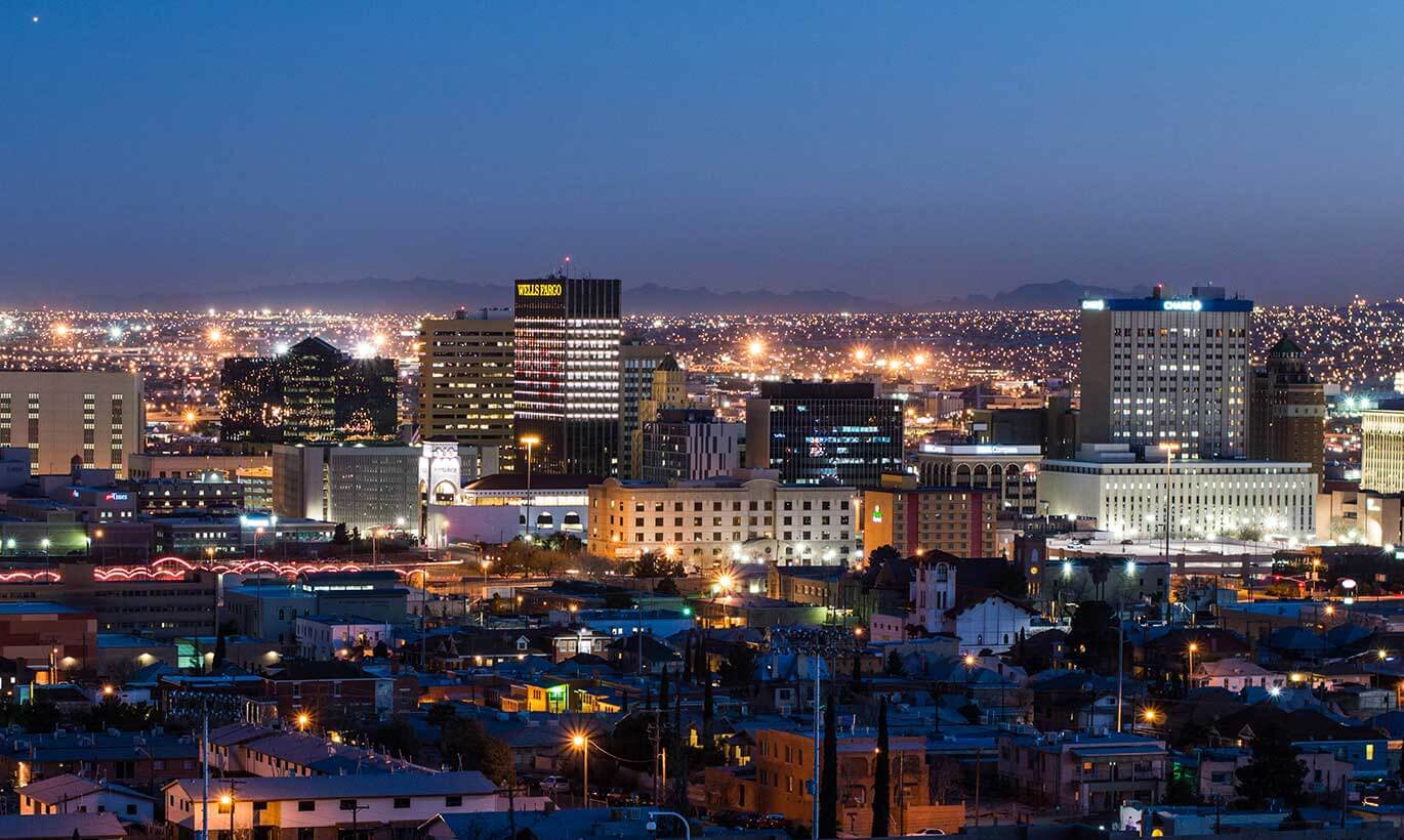 Downtown El Paso is brightly lit up at night with many tall buildings.