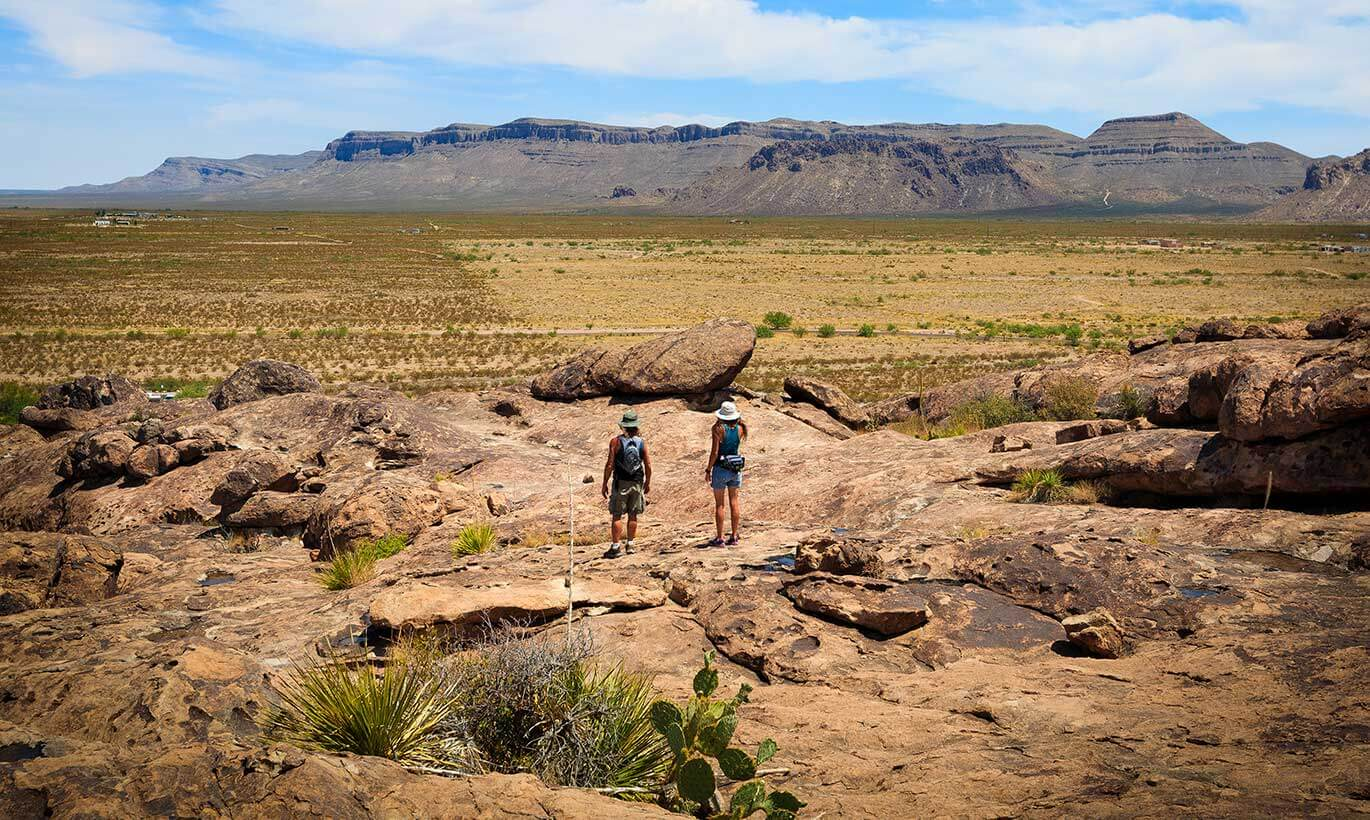 Two hikers wearing hats gaze out at the desert landscape and huge mountains at Hueco Tanks State Park.