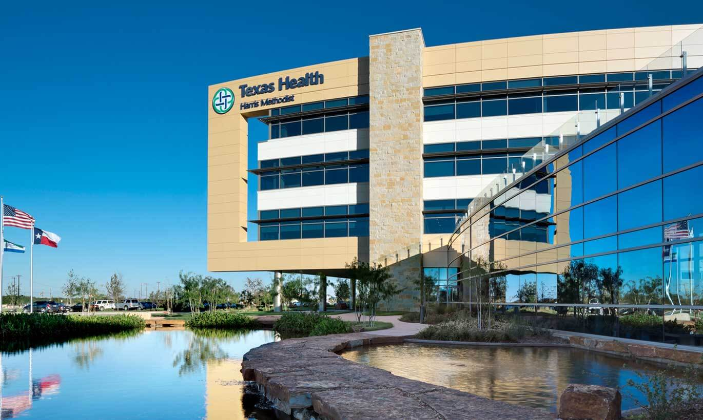 The Texas Health Harris Methodist Hospital in Fort Worth has three flags in front of the building, next to a small pool of water.