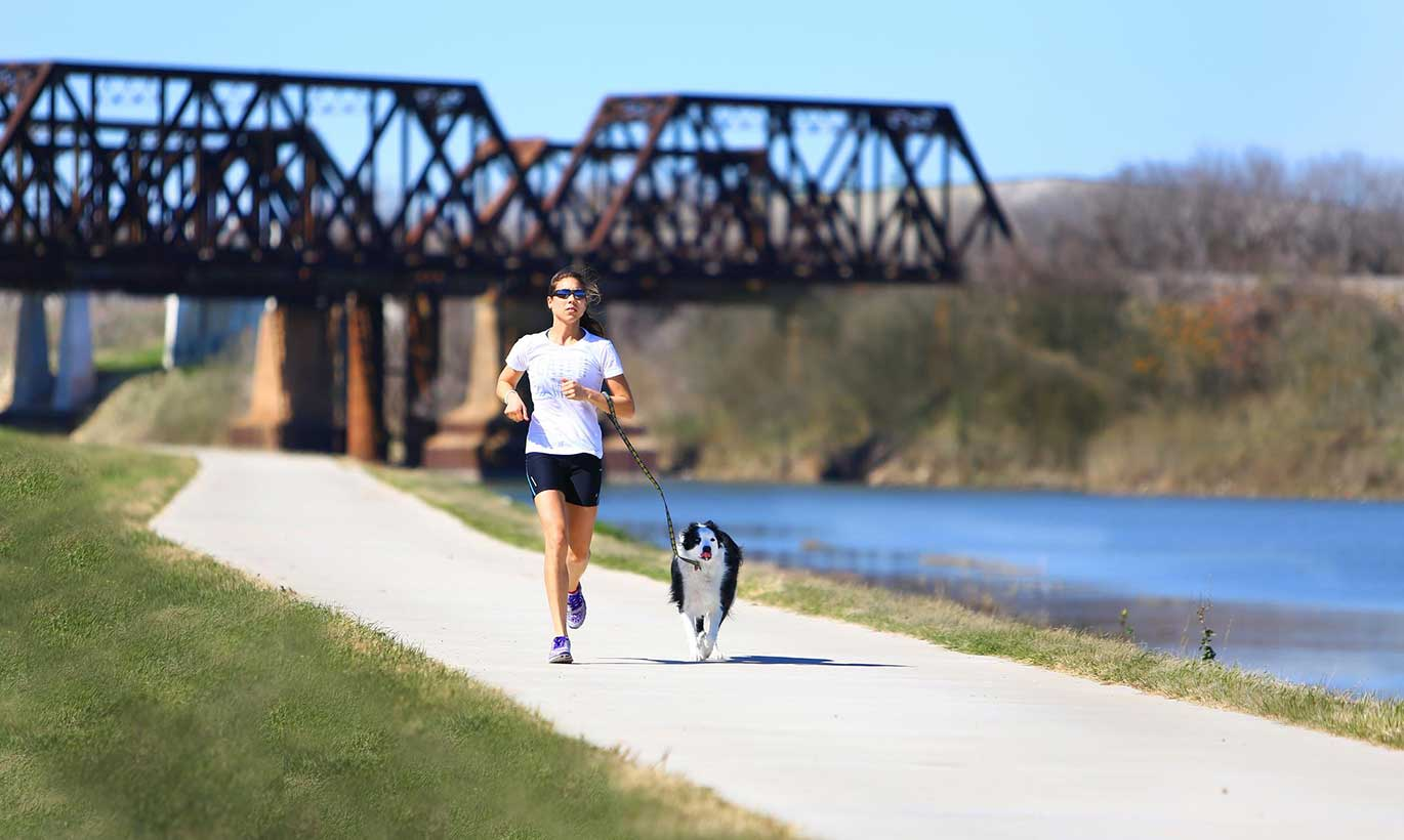 A woman runs alongside her dog on a sidewalk next to a river at Trinity Trails in Fort Worth, Texas.