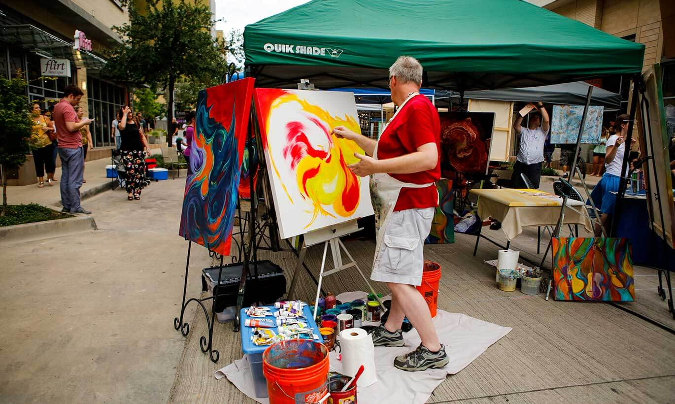 A man paints yellow and red designs on a canvas at the annual pARTy on Crockett artist fair in Fort Worth, Texas.