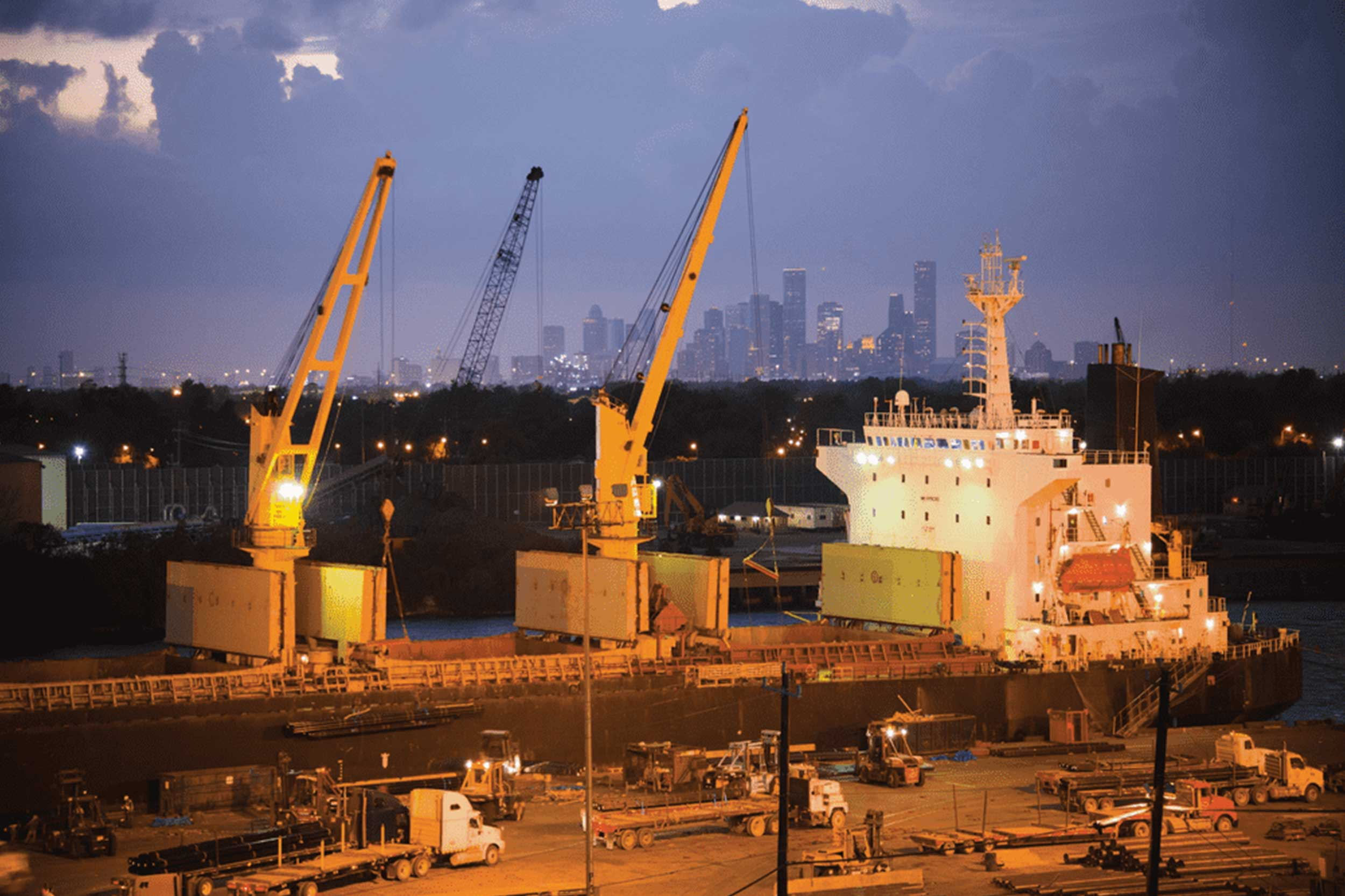 Shipping vessels and trucks operate at night in Port of Houston, Texas.
