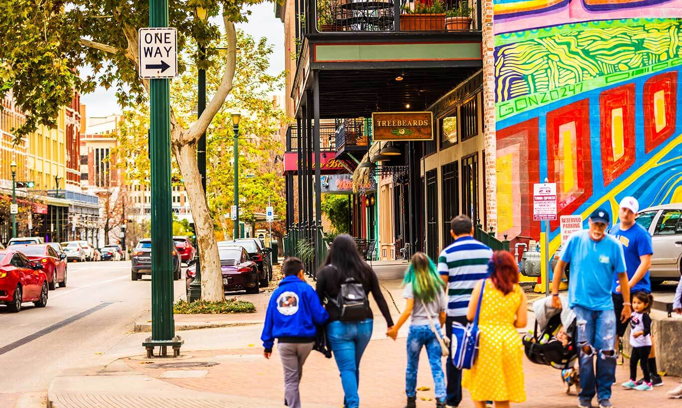 A family holds hands and walks next to a large colorful mural in downtown Houston, Texas.