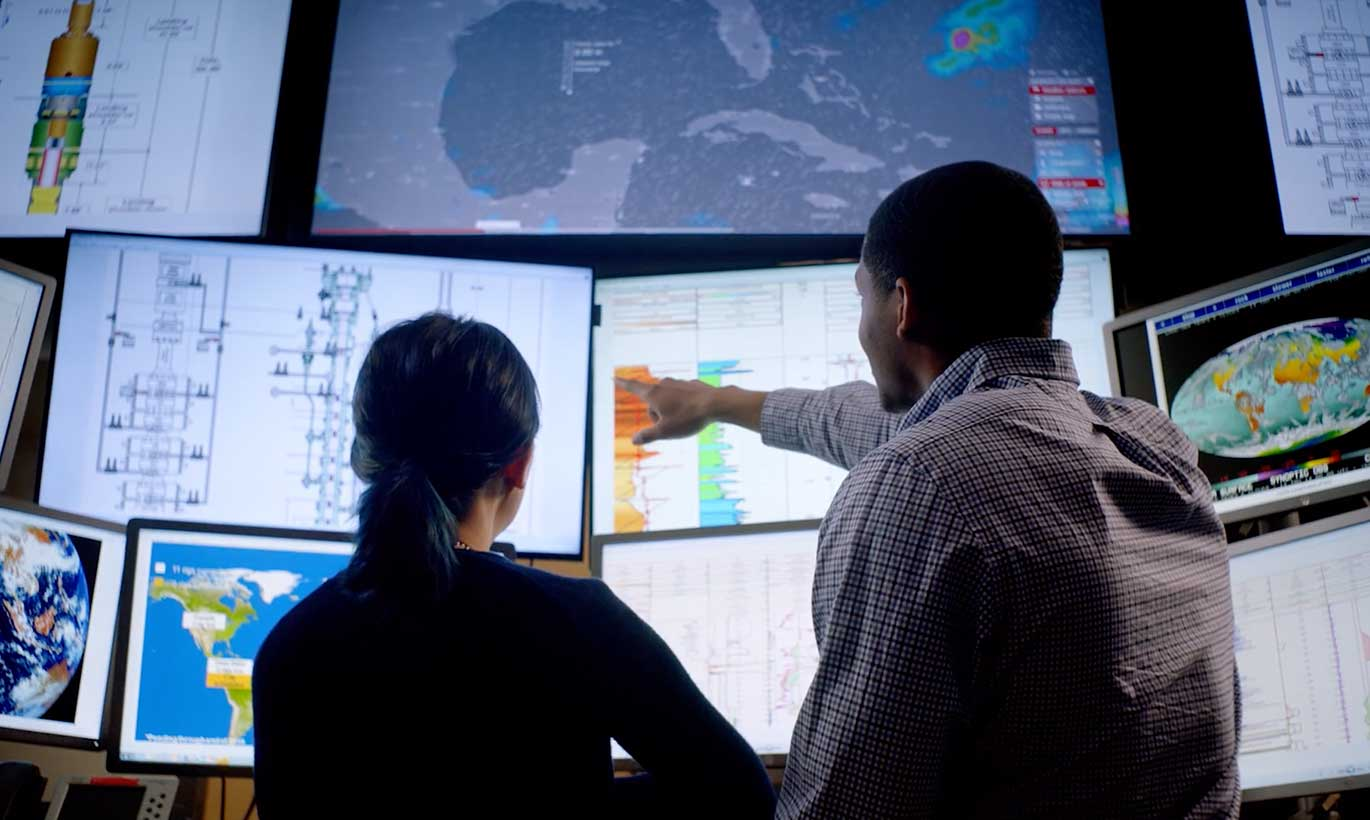 A man and woman point out important data and statistics on energy graphs and maps in Houston, Texas