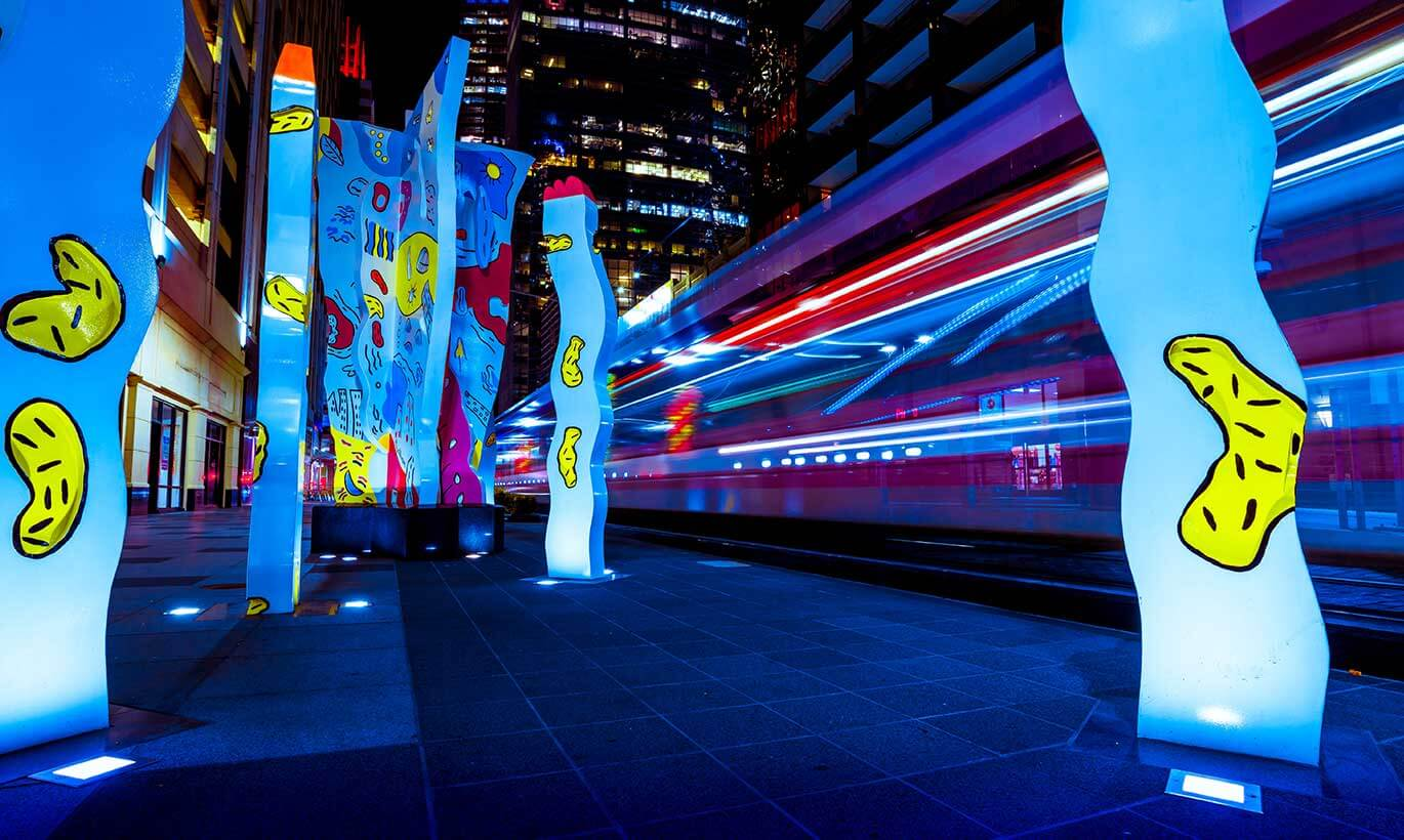 Street art in the Avenida Houston entertainment district lights up with bright blue and yellow colors at night.