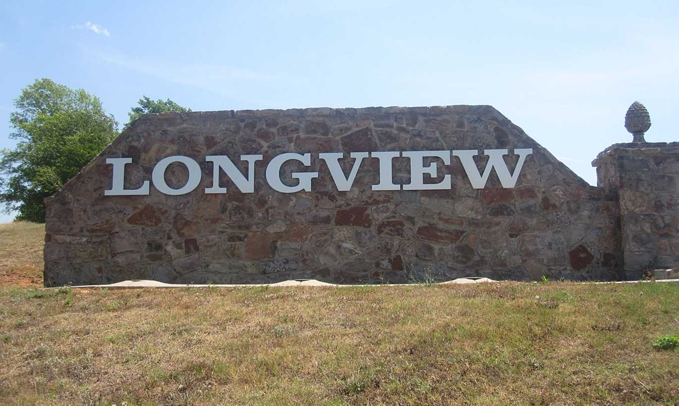 A stone sign depicting the name of the city of Longview, Texas sits on a hill.