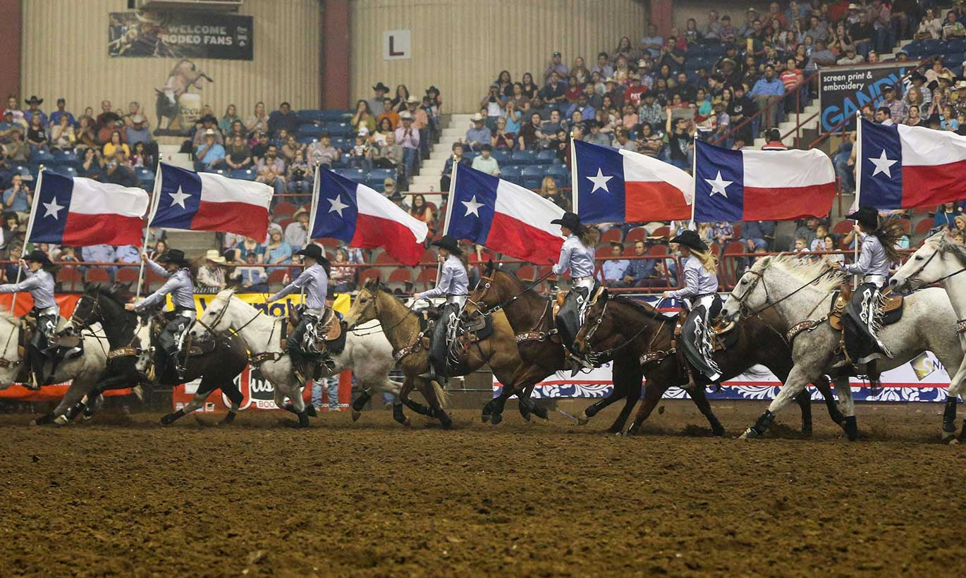 Cowboys on horseback hold large Texas flags at the San Angelo Rodeo while a large crowd watches from above.