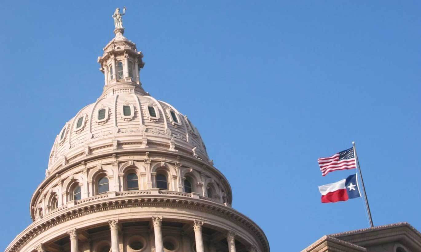 The dome of the Texas Capitol building with the United States and Texas flags flying in the sky in Austin, Texas.