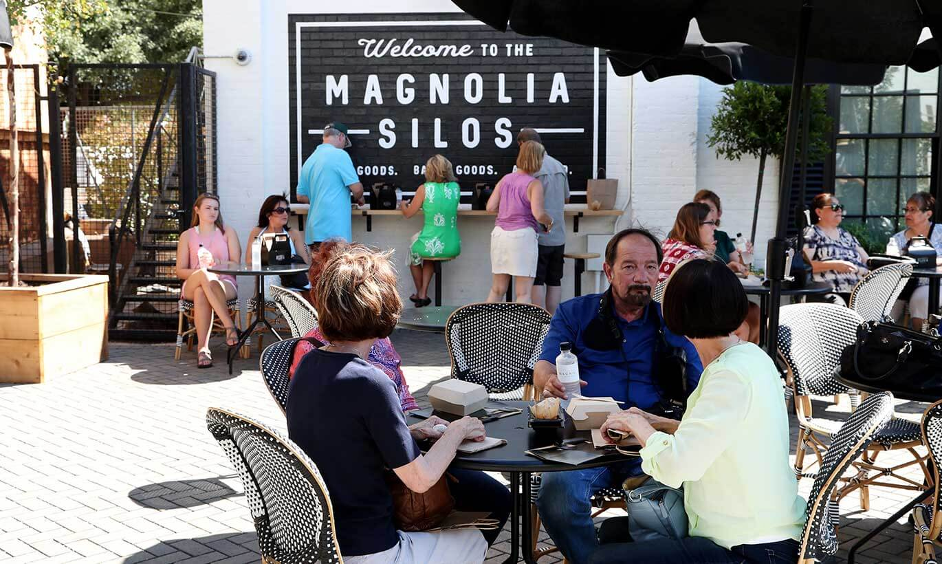 People sit outside to eat at tables at Magnolia Market in Waco, Texas.