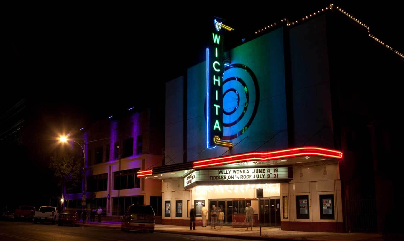 A local movie theatre in Wichita Falls, Texas is lit up at night with people standing at the entrance.